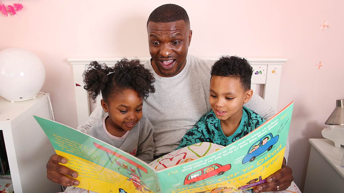 Dad and kids reading Welsh-English version of Car Car Truck Jeep