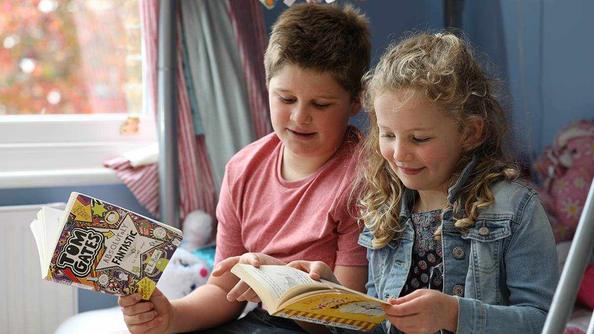Brother and sister reading at home