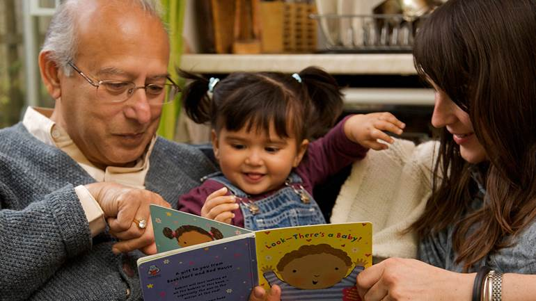 Grandparent and baby reading