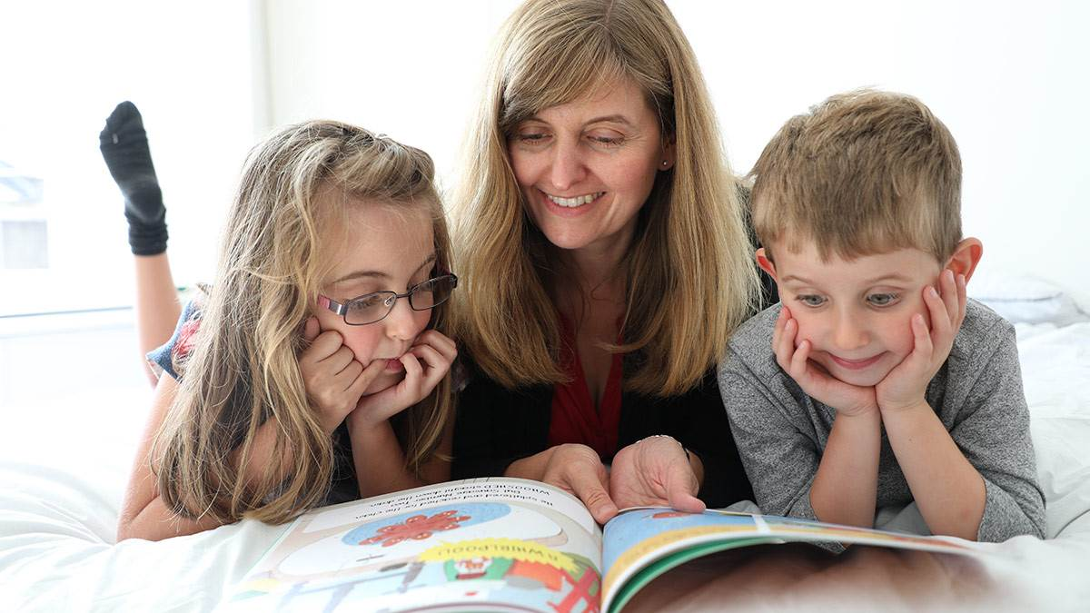 A mother and two children reading together
