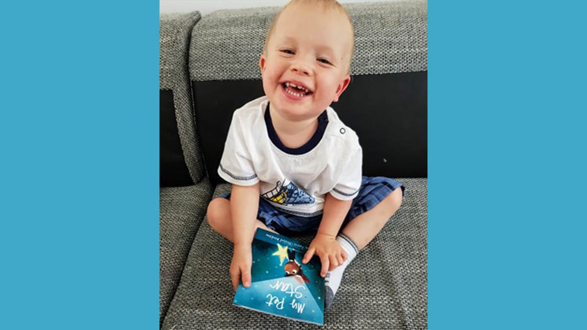 Laughing boy with his copy of My Pet Star
