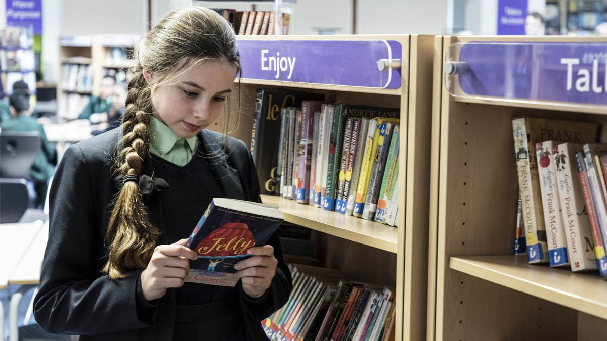 A girl looking at a book in a school library