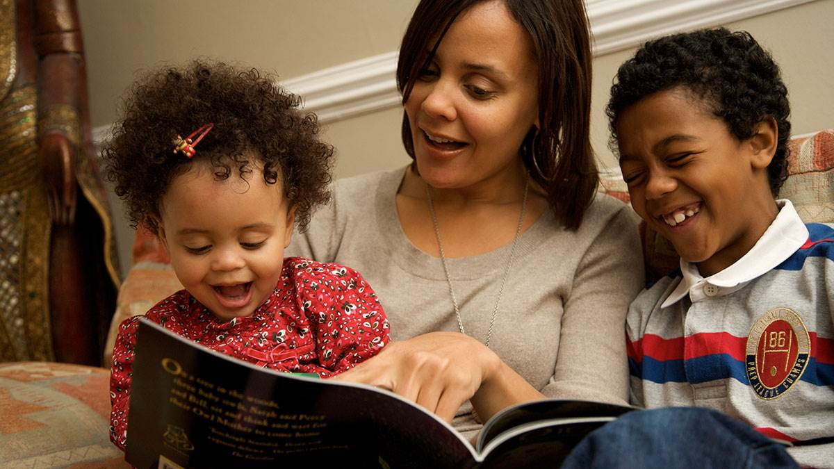 A mother enjoys reading with her daughter and son