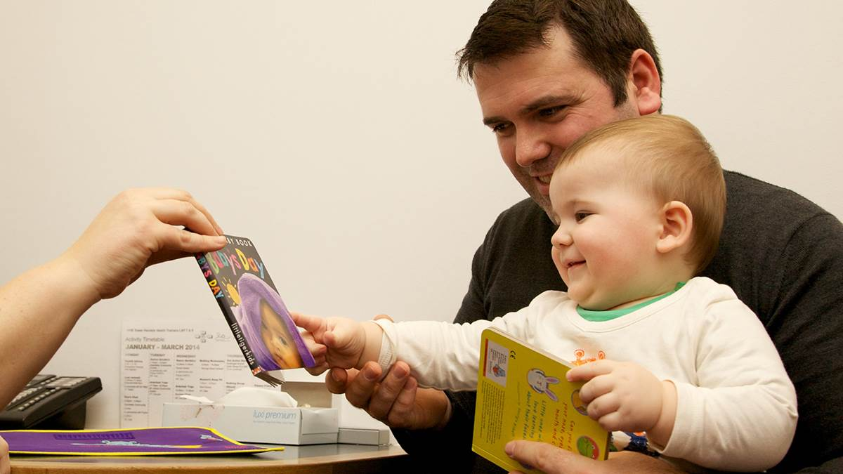 health visitor hands book to dad and baby
