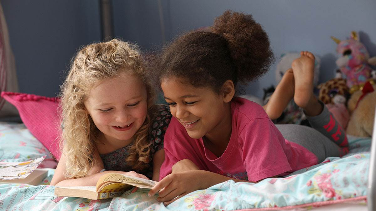 Children reading on a bed together